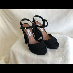 black leather peep-toe pumps.